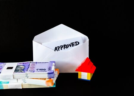 High angle shot of a lego house near opened white envelope, approved word on the paper inside and money bundles in foreground Imagens