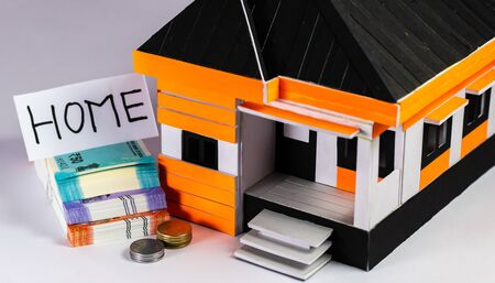 Home loan concept shown with bundles of money, house model and coins on white background
