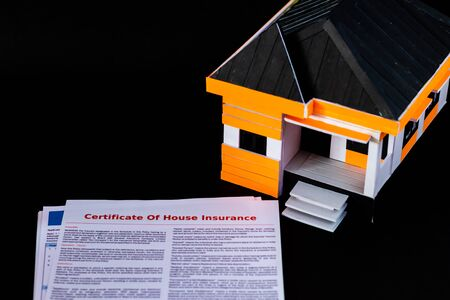 House Insurance Certificate papers on black background with a house model Imagens