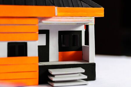Low angle close up shot of a craft made house model with defocused black background