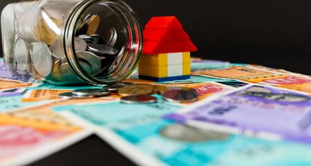 Low angle close up shot of a glass jar opened and fallen with a lego house toy and money notes