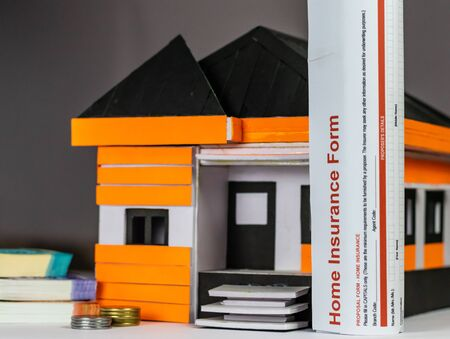 Low angle close up shot of a house model with money bundles, coins and Home Loan Form rolled put vertically upright