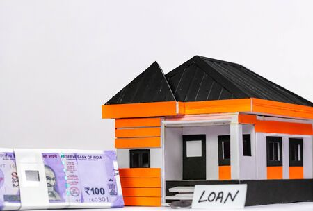 Low angle close up shot of a house model, money, and LOAN word written on paper