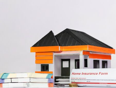 Low angle close up shot of a money bundles, coins, house model and Home Insurance Document Imagens