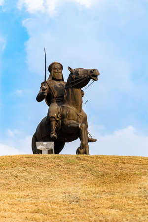 Sikh Warrior statue on horse and holding a sword against sky in the background. memorial park concept-2
