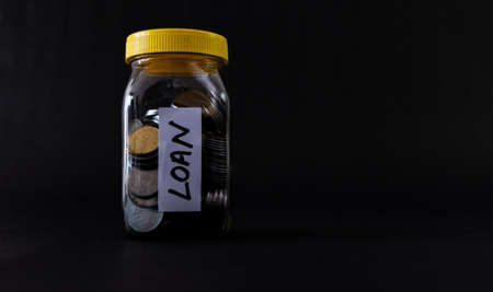 Coins in a glass jar with Loan word labelled on black background with copy space