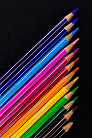 Top close up shot of beautiful color pencils arranged diagonally over a black background in Fine Art concept Imagens
