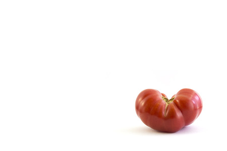spacing: tomato in heart shape on white background with spacing for caption