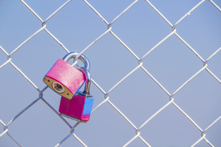 fench: couple pink padlock on metal fench