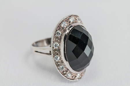 black onyx: Old silver ring with black-colored precious stone on white satin background. Stock Photo