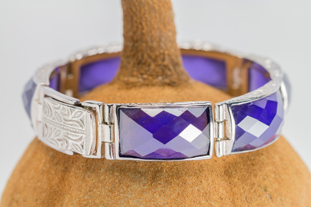 bangle: Close up, old silver bangle with an amethyst, set on mahogany seed background.Handmade