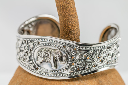 jewelry: Old silver Bangle, elephant pattern Thai style, set on mahogany seed background.