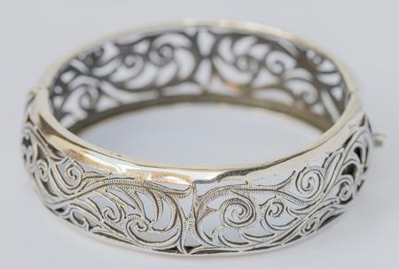 bangle: Macro image, old silver Bangle, vine patterns on a white Background. Handmade Stock Photo