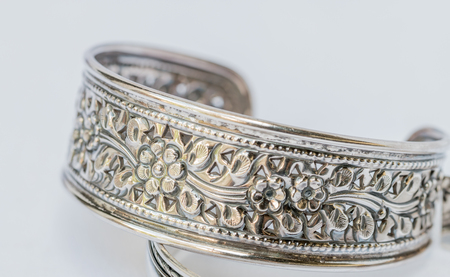 bangle: Macro image, old silver Bangle, floral patterns on a white Background. Handmade