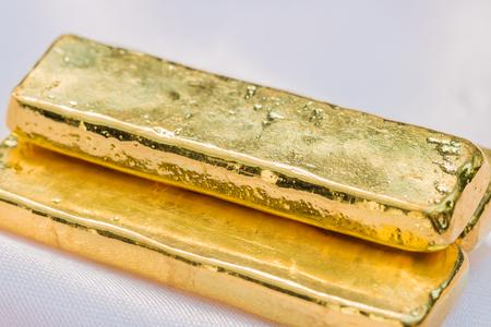 ingot: Gold bars (gold ingot) on a soft pink cloth background. Macro. Stock Photo