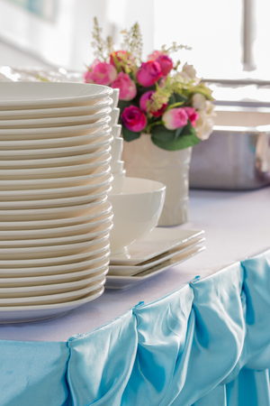 cater: Clean dishes on the table, prepared for buffet party, on light background. Stock Photo