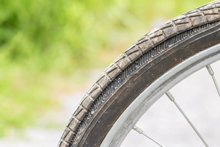 Old bicycle wheel, with leak rubber, damage tires, on green blurred background. Stok Fotoğraf