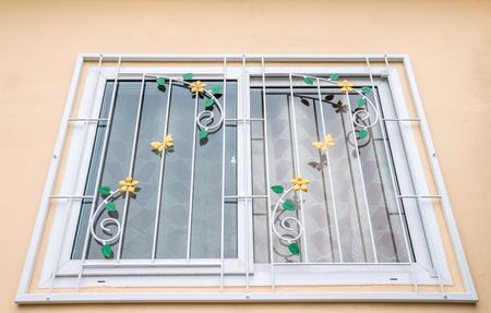 Padrão de aço curvado (ferro forjado) em uma janela de vidro, na parede laranja, para decoração e proteção de uma casa.