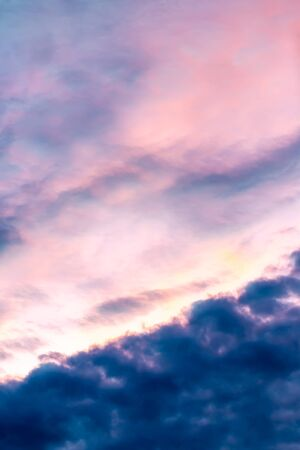 Abstract blurred background, colorful dramatic sky, blue, magenta, dark clouds in twilight, looks like a watercolor painting, vertical image.