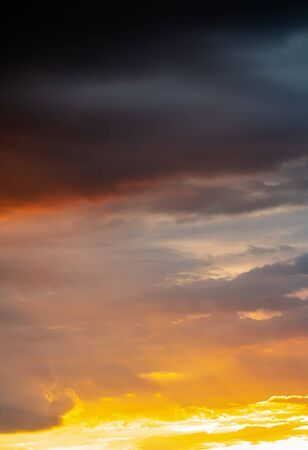 Colorful dramatic sky in evening, blue, magenta, golden, grey, orange and storm cloud, with sunlight breaking through clouds, in soft blurred style, vertical image.