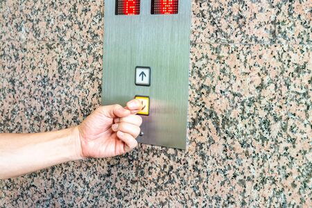 New normal, press the elevator button with the back of finger, for COVID-19 coronavirus crisis prevention. Zdjęcie Seryjne
