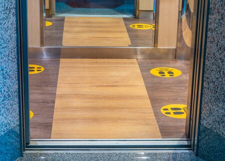 New Normal, floor marking of standing position in the elevator, with text caution to respect social distance, for COVID-19 coronavirus crisis prevention. Zdjęcie Seryjne