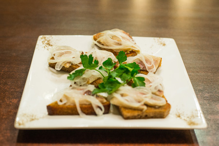 Toasts with herring and onion decorated with parsley Stock Photo