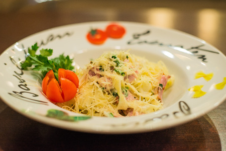 Italian dish pasta Carbonara on a white plate decorated with tomatoes
