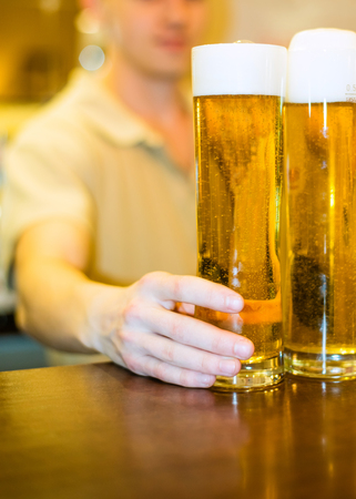 Barman pours beer into a glass at the bar