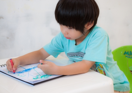 Boy painting with crayon on a drawing book Stock Photo - 16003229