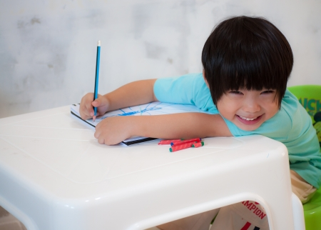 Boy painting with crayon on a drawing book  Stock Photo