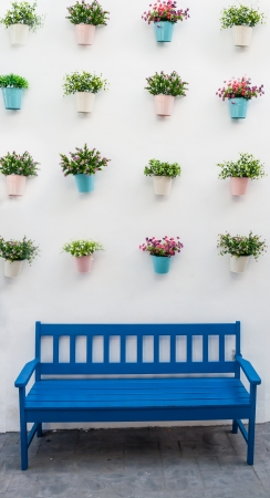 Blue bench with flower pots on background wall  Stock Photo - 17118905