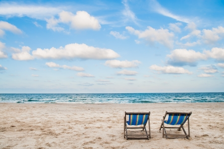 Beach chairs on white sand beach with cloudy blue sky