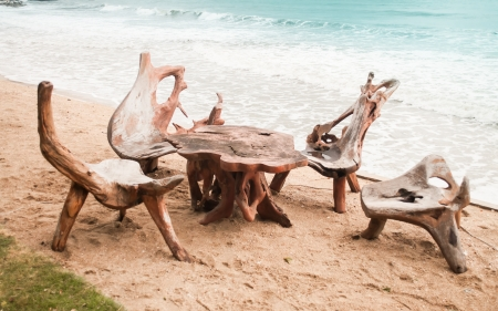 The chairs and table made from tree root on the beach