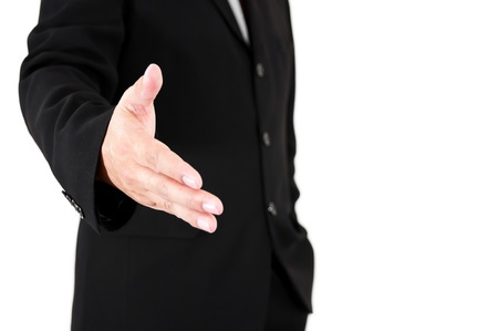 A man in black suite reaching out to shake your hand photo