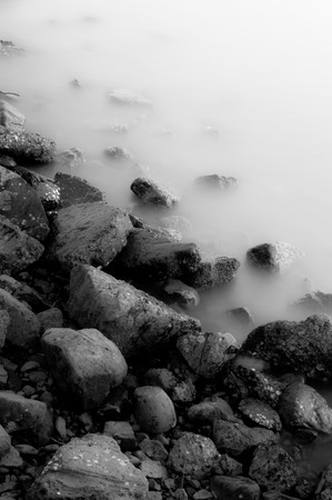 The rock coast with smooth wave in black and white