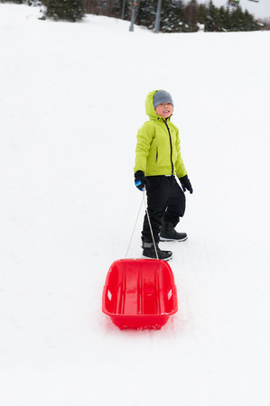 sledging: Cute young boy smiling while he is sledging