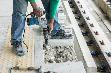 drill floor: Worker with pneumatic hammer drill equipment breaking concrete floor at construction site