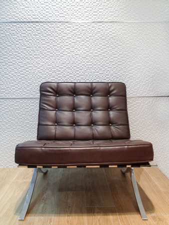 The modern style leather chair on wood floor and white ceramic wall background