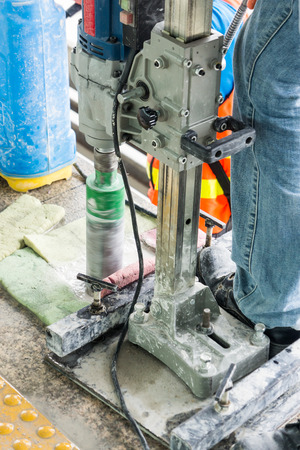 drill floor: Worker drilling holes in concrete floor at construction site