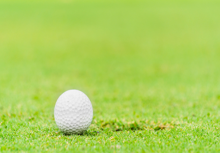 A golf ball near the lip of cup
