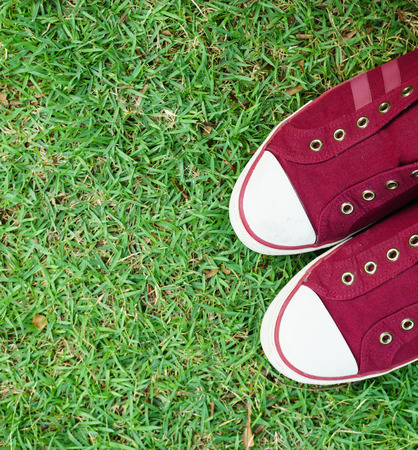 A pair of red shoe on grass in a park Stock Photo