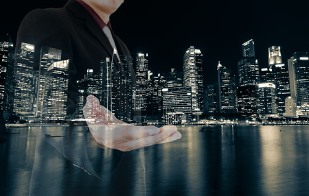 Double exposure of business man  and night cityscape as background