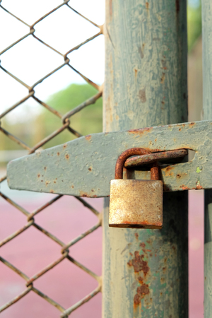 solid wire: Old bolt and padlock on the door tennis court