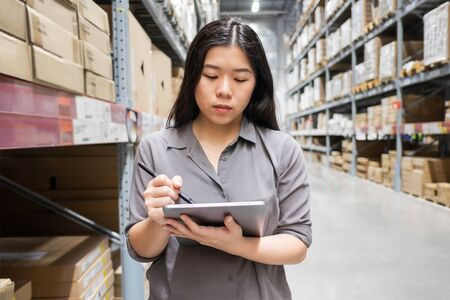 Beautiful young Asian woman auditor or trainee staff work stocktaking with computer tablet at warehouse store, Asian working business woman concept