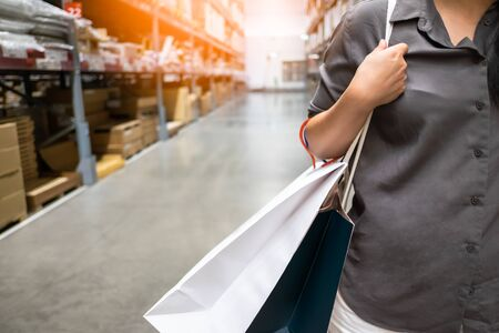 Asian woman holding shopping bag at warehouse store, lifestyle concept Standard-Bild