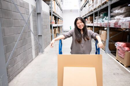 Happy beautiful young Asian woman customer or staff worker pushing trolley or picking cart in warehouse store with blur background of boxes on shelf, self service shopping concept Standard-Bild