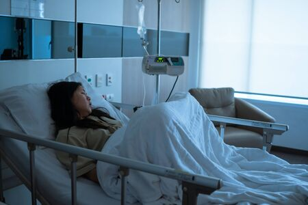 Young sick Asian patient woman lying on bed in hospital ward, sad and serious of disease Standard-Bild