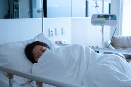 Asian female patient sleeping on hospital bed to recovering sickness