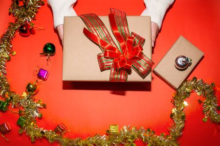 female hand in sweater holding a red present box for Christmas, New Year, Valentine'a day on red background, top view Standard-Bild